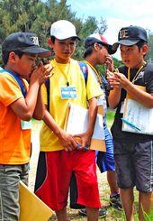 道路脇に自生していた草を摘み、草笛に挑戦する子どもたち=5月31日、伊江村東江上区