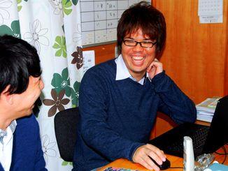 就労移行支援施設「コミュッと!」のスタッフと冗談を言い合って笑う仲松誠悟(右)=15日、うるま市田場