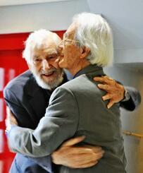 50年ぶりの再会で抱き合う平良修牧師(右)とウィリアム・エルダー宣教師=20日、宜野湾市・沖縄キリスト教センター