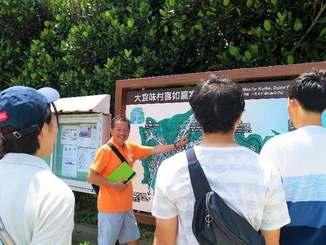 大宜味村喜如嘉の特徴を地図を使って観光客に説明するオクマ プライベートビーチ&リゾートの大山さん(同ホテル提供)
