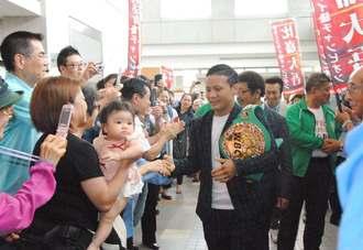 多くの市民から拍手で迎えられ、笑顔で応える比嘉大吾選手(中央)=9日午後2時、浦添市役所