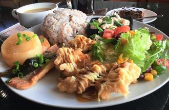 サイドウェイズの日替わりランチプレート。若鶏の天ぷら(手前右)と赤魚の煮込み(手前左)にサラダや雑穀米、和え物など盛りだくさんのプレート