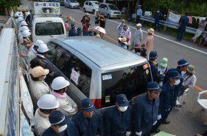 M1地区で常駐を始めた防衛局職員(左)と護衛する機動隊員(手前)=16日午後3時21分、東村高江