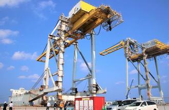 台船「天佑」に積み込まれるガントリークレーン1号機(左)=25日、那覇港新港ふ頭地区