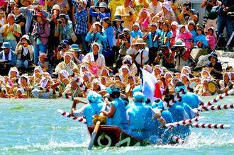 手招きをしながら爬龍船を出迎える女性たち=20日、大宜味村塩屋(伊藤桃子撮影)