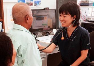 70代男性を診察する小澤萌さん。現在の県立離島診療所では、唯一の女性医師だ=北大東村(本人提供)