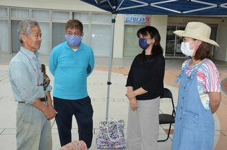 具志堅隆松さん(左)の激励に笑顔を見せる金城博俊さん(左から2人目)、大田弥生さん(同3人目)、津嘉山恵子さん=3日、豊見城市役所前