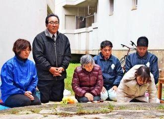ユナパチク壕の東側入り口だった古井戸に向かい祈りを捧げる並里千枝子さん(左から3人目)や島袋秀幸村長(同2人目)ら=24日、伊江村西江上
