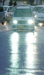 雨が降りしきる中、水しぶきを上げて走る車=21日午後5時半ごろ、名護市宮里