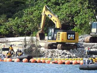 護岸工事のため、クレーンで吊した石材が波打ち際に次々と投下された=15日午前9時10分、名護市辺野古・米軍キャンプ・シュワブ沿岸部
