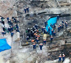 首里城火災で全焼した正殿の北側を調べる消防隊員や県警の捜査員=4日午前11時16分、那覇市首里当蔵町(小型無人機で撮影)