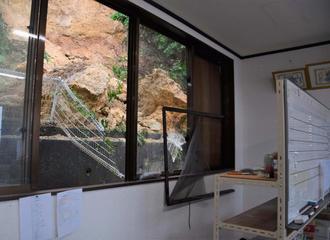 土砂の崩落で割れた事務所の窓=24日午後1時10分ごろ、うるま市大田
