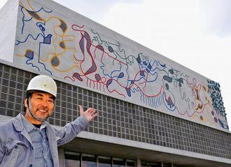 レリーフ「夢想」の完成を喜ぶ彫刻家のゴヤ・フリオさん=19日、西原町の新庁舎建設地
