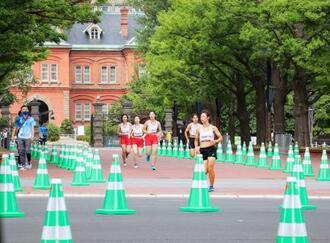 東京五輪マラソンのリハーサルで、北海道庁旧本庁舎(奥)付近を走る選手役のランナーら=1日、札幌市