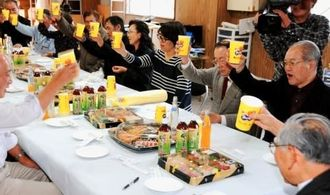 沖縄バヤリース社の解散うちあげ会で、看板商品「バヤリースオレンジ」で創業42年の頑張りに乾杯する社員ら=30日、南城市大里古堅の同社