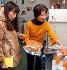 座間味久美子代表(右)からクワンソウの特徴を聞く柿沢安耶さん=12月27日、今帰仁村上運天・今帰仁ざまみファーム