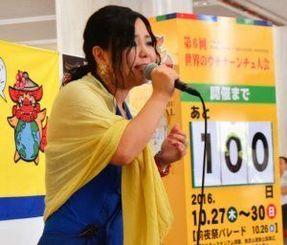大会テーマソングを披露する花城舞さん=19日、沖縄県庁