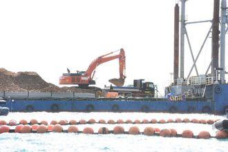米軍キャンプ・シュワブ沿岸のK9護岸で始まった台船の土砂をダンプに積む作業。ダンプは基地内を通って土砂投入の現場に向かう見込み=12月14日午前、沖縄県名護市辺野古