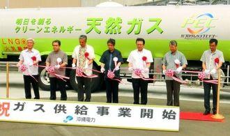 液化天然ガス(LNG)の供給事業開始を記念し、沖縄電力の大嶺満社長(中央)ら関係者がテープカットした=中城村、吉の浦火力発電所