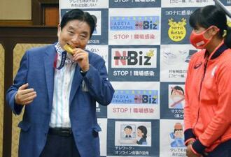 首に掛けられた後藤希友(右)の金メダルをかじる河村たかし名古屋市長=4日午前、同市役所