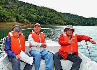 羽地ダム建設で水没した集落付近で、当時の様子を説明する崎濱秀徳さん(右)と島袋徳次郎さん(中)。左は、渡慶次一夫支所長=名護市田井等