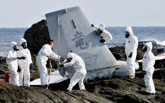 墜落の衝撃で大破した尾翼部分の解体作業をする米軍=16日午後1時35分、名護市安部の海岸(山城知佳子撮影)