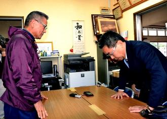 部品落下を受けて玉城自治会長(左)に謝罪する沖縄防衛局の中嶋局長=9日、伊計自治会