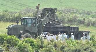 炎上したヘリの事故現場で、土壌調査へ向けたサンプリングを行う県と防衛局の調査員ら=20日午前11時19分、東村高江