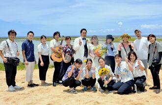 儀保龍一さんと萌さん夫妻(中央)の結婚式を作り上げた学生やスタッフ=7月10日、読谷村・渡具知ビーチ