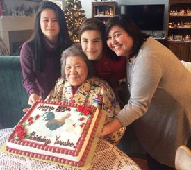 娘や孫たちに囲まれ、酉年にちなんだケーキを前に笑顔の安子ヒューズさん(中央)=米オハイオ州