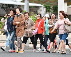 冷たい風が吹く中、厚着して歩く観光客ら=30日午後5時すぎ、那覇市泉崎