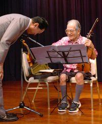 お祝いの演奏をしたバイオリニストの鳩山寛さん(右)に、鳩山由紀夫元首相がお礼を述べた=那覇市のロワジールホテル那覇