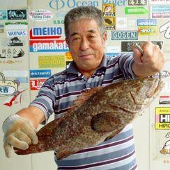 泡瀬海岸で52センチ、2.46キロのミーバイを釣った蔵富秀光さん=13日