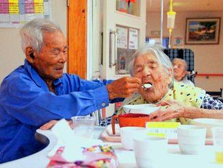 「あーん」と食事の介助をする山城義雄さん(左)とミドリさん=16日、特別養護老人ホームいえしま
