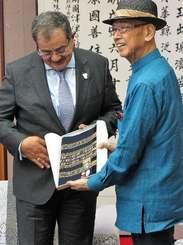 アルムーサウィー駐日イラク大使(左)に沖縄の首里織をプレゼントする翁長雄志知事=20日、県庁