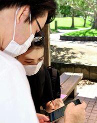 候補者のSNSを見つめる喜舎場悠太さん(左)と當山果鈴さん=3日、西原町の琉球大学