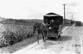 那覇-糸満の約9キロを走った「軌道馬車」。レールは那覇から見て左側に敷かれていたことから、この馬車は那覇に向かっている。右奥には記者が取材に使ったフォード車が写っており、糸満に向かう道中で馬車とすれ違った際、撮影したとみられる(写真:朝日新聞社)