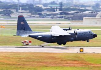 右翼から白い霧状の燃料を放出しながら着陸するC130輸送機=21日正午ごろ、米軍嘉手納基地(読者提供)