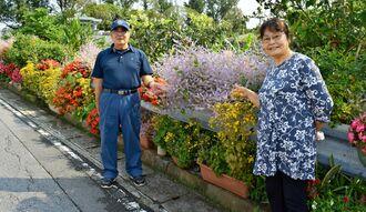 咲き誇る花を手にほほ笑む上地義次さん(左)・絹代さん夫妻=9日、町嘉手納