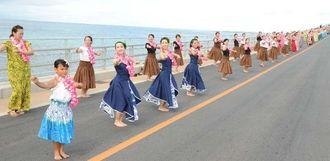フラのギネス記録に挑戦し、笑顔で踊る参加者=3日午前9時すぎ、伊良部大橋