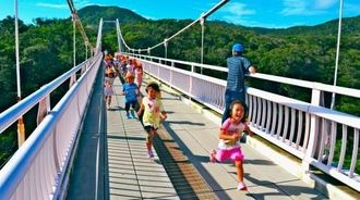 外周路のつり橋「聖紫花の橋」を元気いっぱい駆け抜ける子どもたち=石垣市登野城