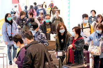 新型コロナウイルス感染予防でマスクをつけ、国際線到着ロビーを出る中国人観光客ら=27日午後、那覇空港(下地広也撮影)