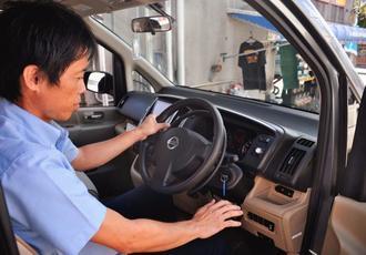 ハンドルの右横に取り付けられた手動補助ブレーキの操作方法を説明する高里健作代表=宜野湾市・タイヤランド沖縄