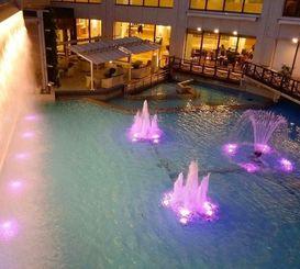 ピンクリボンの日に合わせてライトアップされた施設内の噴水(同社提供)