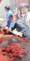 昼食時、肉の焼けるいい香りが漂った「もとぶ牧場フェア」会場=17日午後0時半、那覇市・タイムスビル