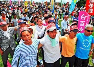 肩を組み「沖縄を返せ」を合唱する大会参加者=15日午後、那覇市おもろまち・新都心公園