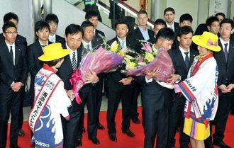 歓迎セレモニーで花束を受け取るヤクルトの小川淳司監督(左)と比屋根渉選手=30日午後0時半すぎ、那覇空港