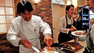 ピザハウス60周年で料理を振る舞った坂井シェフ(左)と坂本社長(左から2人目)=12日、浦添市のピザハウス