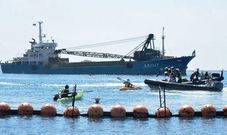 「K9」護岸に向かう砕石船(奥)に抗議しようとオイルフェンスを越えたカヌーが、海上保安官に拘束される=2018年5月16日、沖縄県名護市辺野古・キャンプ・シュワブ沖