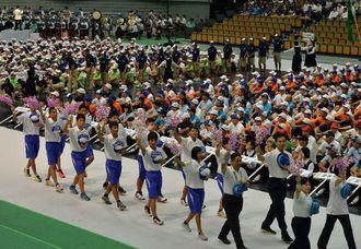 デンファレの花を手に入場行進する沖縄県選手団=28日午前10時20分、和歌山県和歌山市・和歌山ビッグホエール